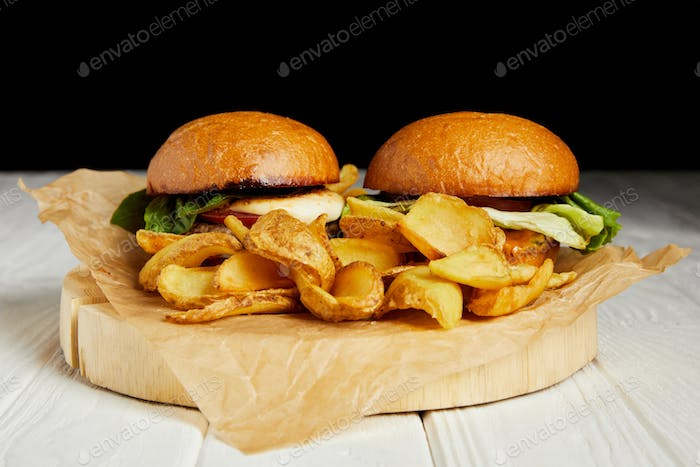Hamburgers and french fries served on craft paper on white table