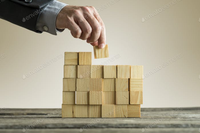 Businessman building a structure with wooden cubes on table surf