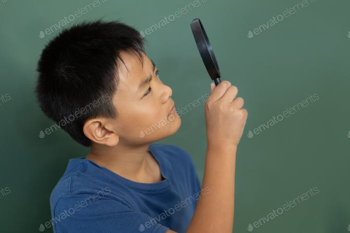 Schoolboy looking through magnifying glass against greenboard in a classroom at elementary school