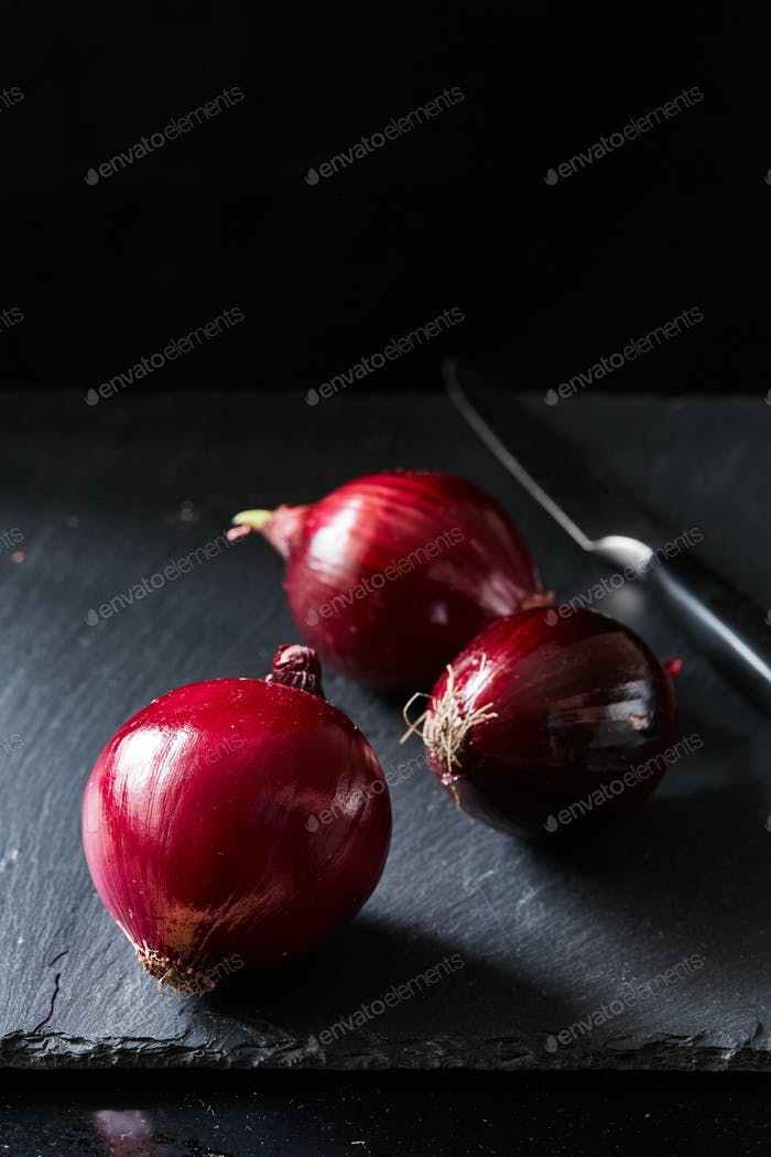 Red spanish onion with kitchen knife on slate backdrop