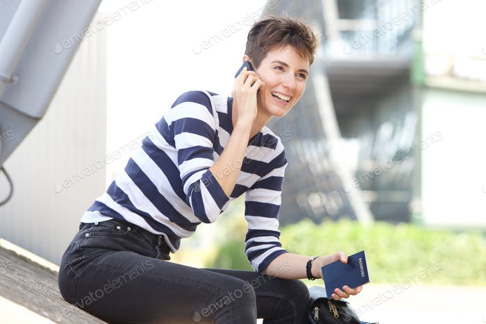 happy young woman sitting outside with cellphone and passport