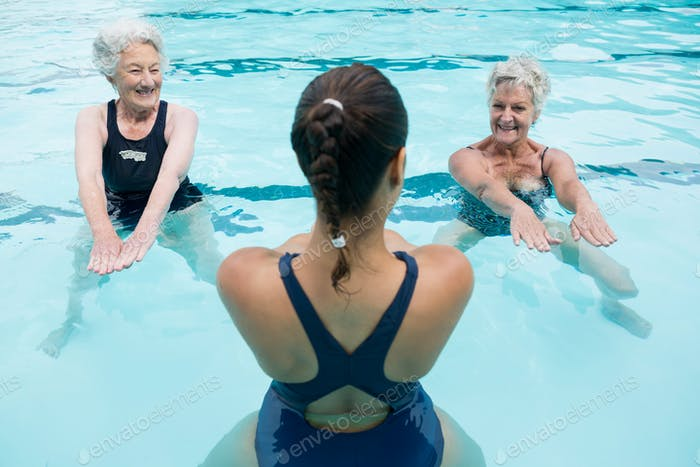 Female trainer with senior women exercising in swimming pool