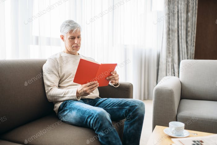 Adult man with notebook sitting on couch at home