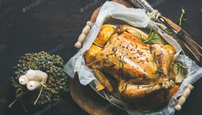 Close-up of roasted chicken with oganges, bulgur and rosemary