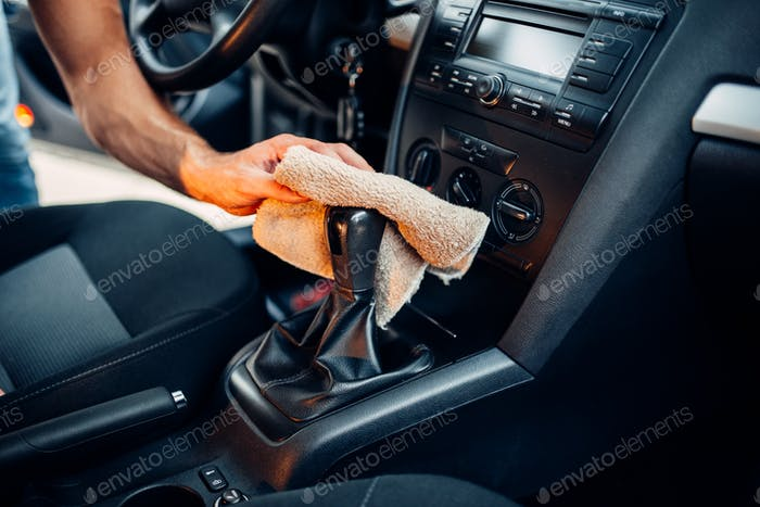 Male hands cleans car interior on carwash station