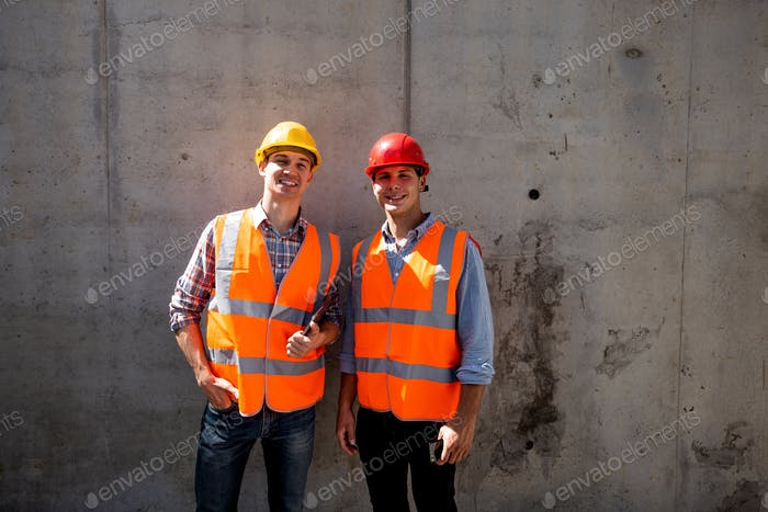 Structural engineer and architect dressed in orange work vests and helmets stand on a concrete wall