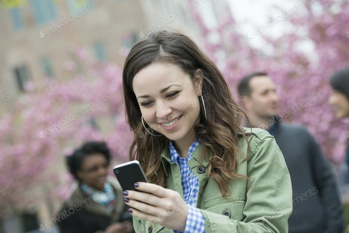 A young woman checking her smart phone for messages in the park