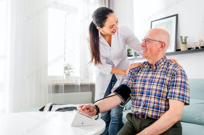 Krankenschwester besucht älteren Mann zu Hause, die Blutdruckmessung durchführt