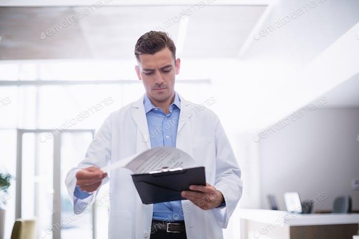 Doctor standing with clipboard in corridor