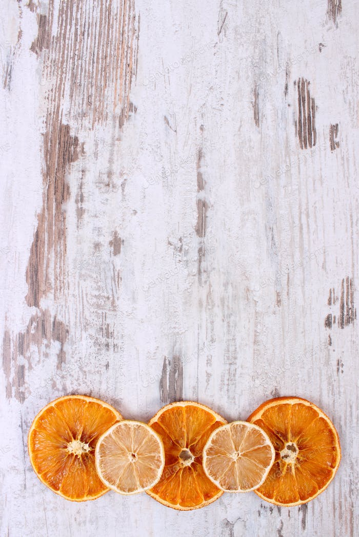 Slices of dried lemon and orange on old wooden background, copy space for text