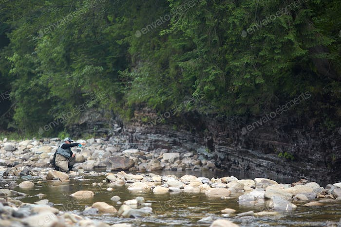 Competent fisherman sitting on stone fly fishing in river