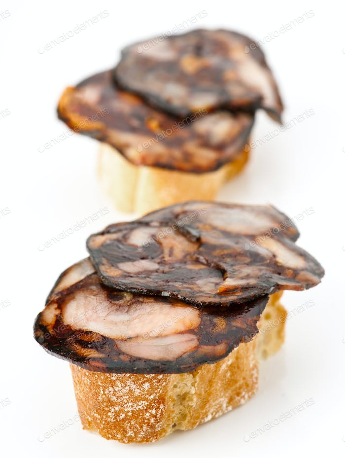 thin slices of Iberian morcilla on bread in white base