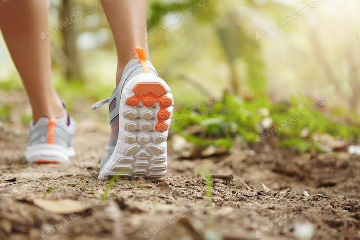 Sports, fitness, nature and healthy lifestyle concept. Young female runner wearing sneakers or runni