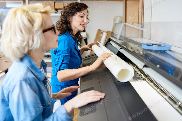 Women Changing Paper in Printing Press