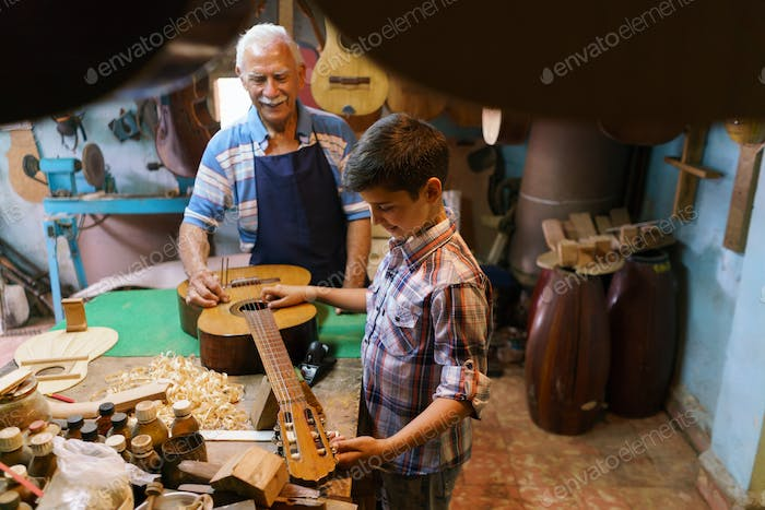 Lute Maker Grandpa Teaching Boy Grandson Tuning Guitar