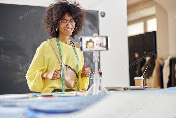 Smiling African-American teacher shoots tutorial for fashion design class at table