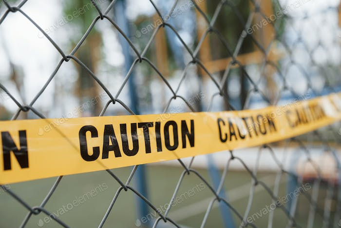 Yellow caution tape on the metal fence at daytime. Crime scene