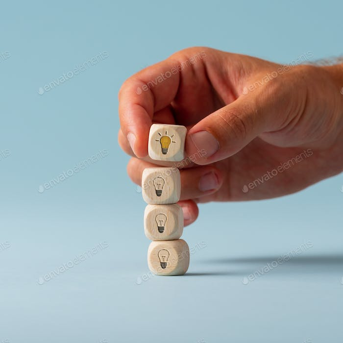 Hand stacking dices with light bulb symbol on them