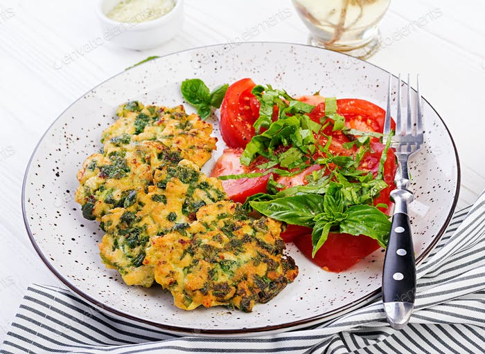 Baked steak chopped chicken fillet with spinach and a side dish of tomatoes salad.
