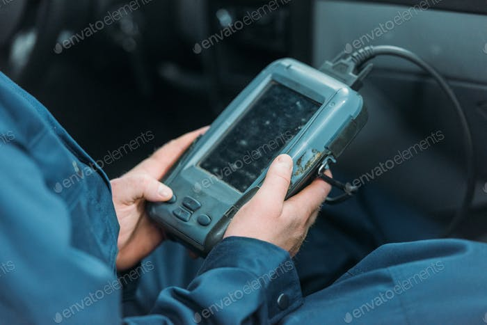 Cropped shot of automechanic using a car diagnostic tool in a service workshop.