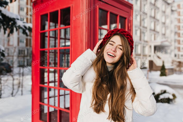 Long-haired lady in knitted beret posing with smile beside phone booth in cold day. Outdoor photo of