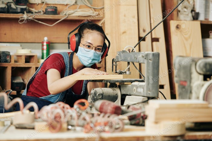 Carpenter cutting wooden planks