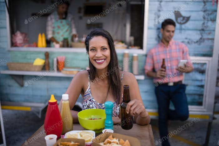 Portrait of beautiful woman holding beer bottle while having snacks in cafeteria