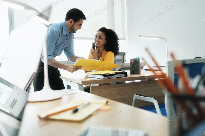 Female Manager Speaking With Mobile Phone And Colleague At Work