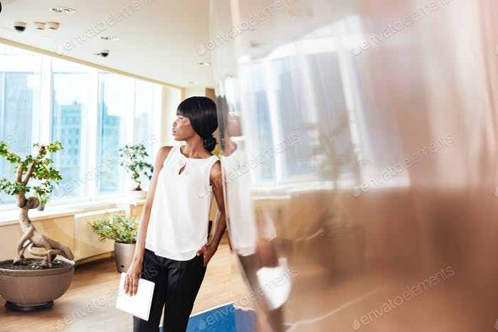 Businesswoman leaning on the wall in office
