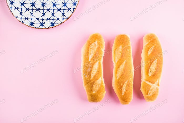 Threen mini baguette on pink background