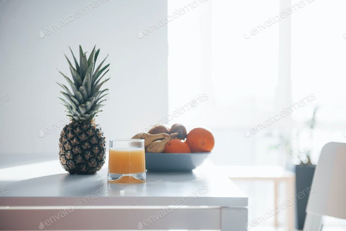 Pineapple, bananas, oranges and glass with fresh juice on the table