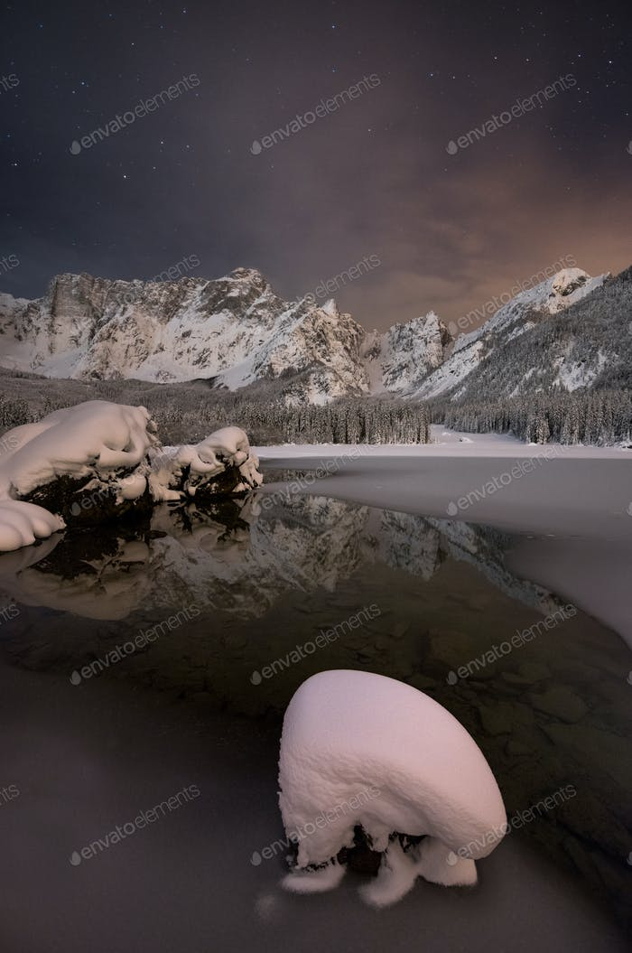 Winter landscape in the mountains by the lake with stars in the sky