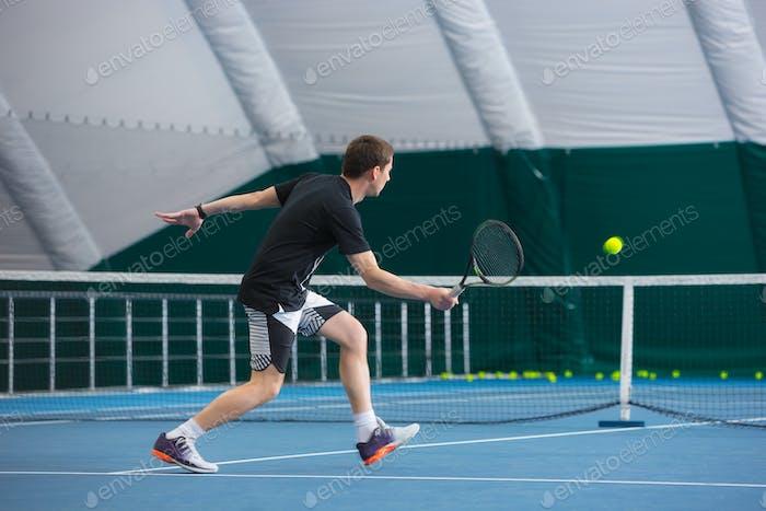 Der junge Mann in einem geschlossenen Tennisplatz mit Ball