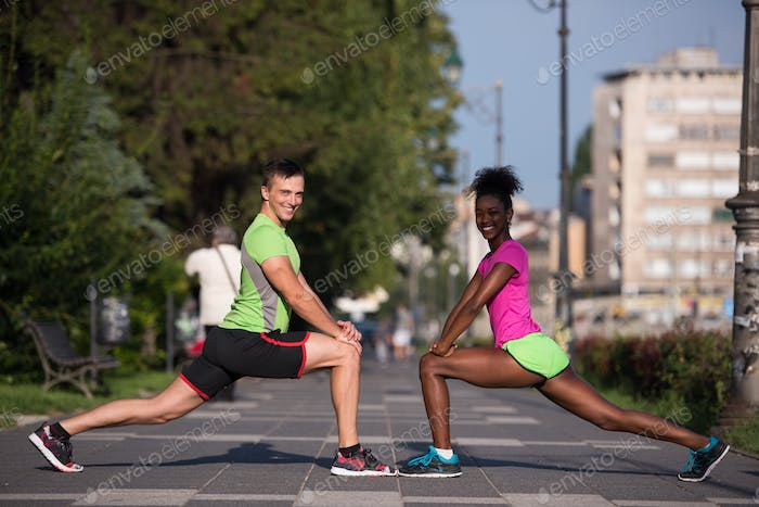 jogging couple warming up and stretching in the city