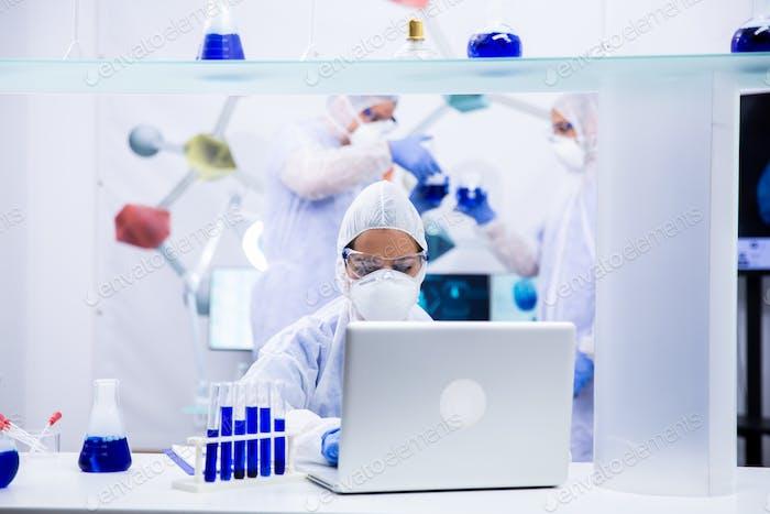 Химик стоит перед ноутбуком с некоторыми пробирками рядом с ним