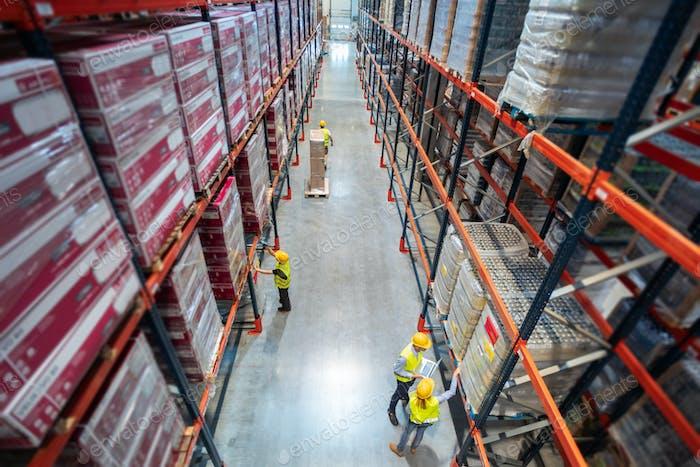 Lagerarbeiter bei der Arbeit zwischen Reihen von hohen Regalen voller verpackter Kartons, Draufsicht