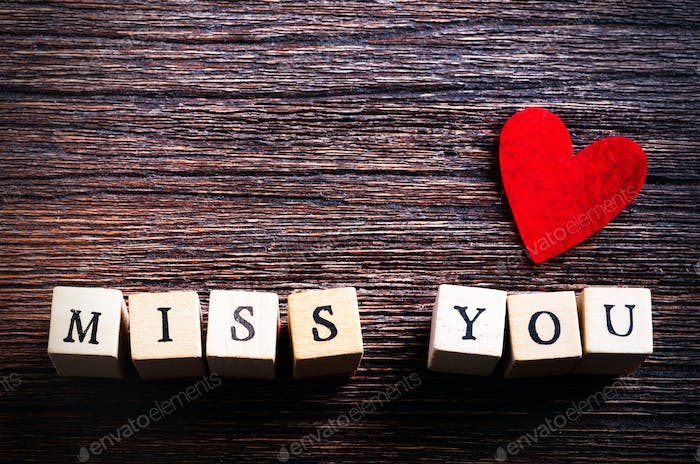 Heart shaped chewing candies and words miss you on cubes, wooden background. Free space for your