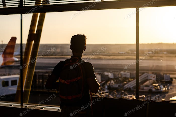 Thoughtful young man looking by the window at a airport terminal
