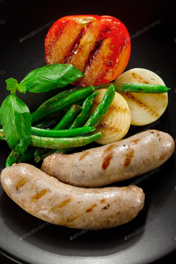 Sausages and fried tomatoes.