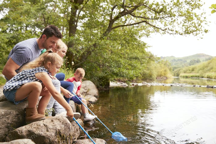 Family Fishing With Nets In River In UK Lake District