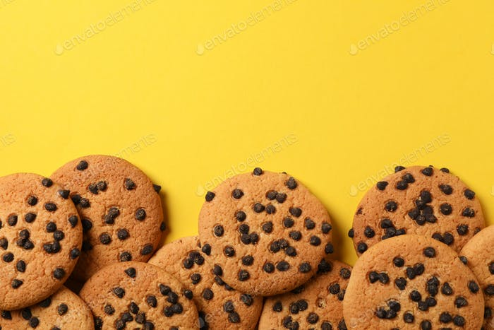 Tasty chocolate chip cookies on yellow background, top view