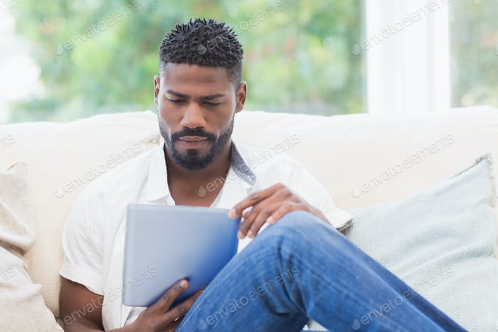 Man using his tablet on couch at home in the living room