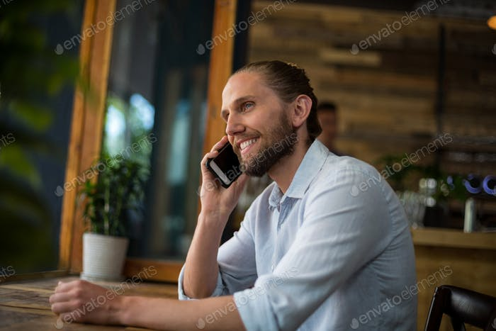 Man talking on mobile phone at café