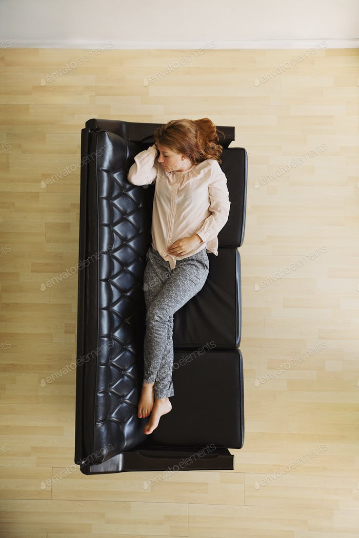 Young woman taking a nap on couch - Indoors