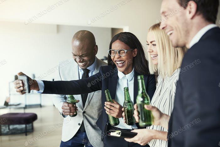 Laughing businesswoman taking selfies over drinks with colleagues after work
