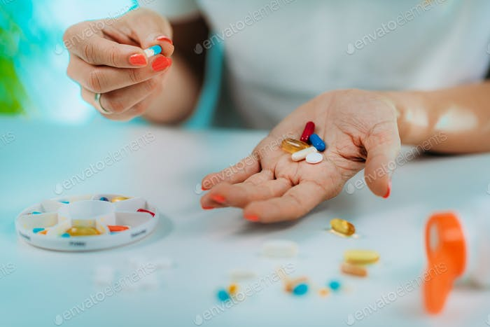 Medicine non-adherence. Woman holding pills in hand.