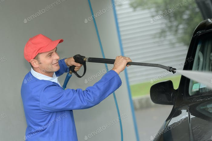 Worker cleaning car with power washer