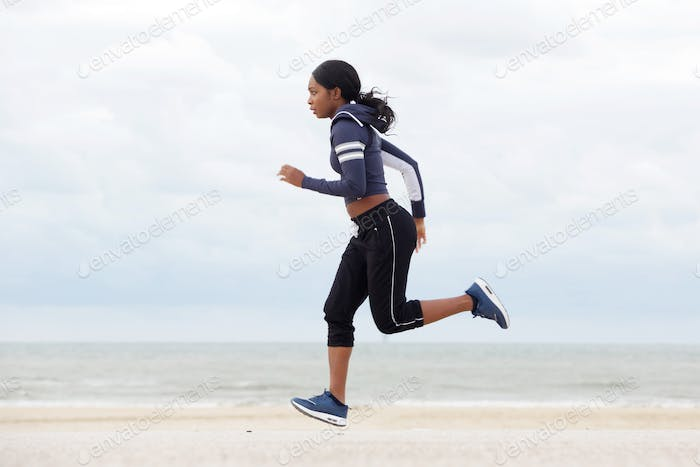 healthy young african american woman running by the beach