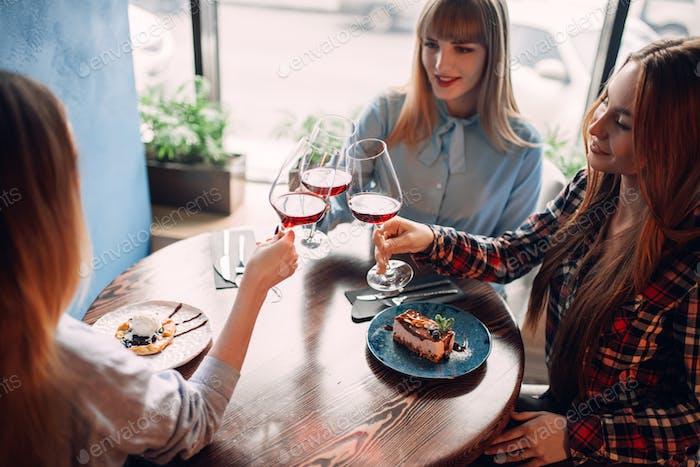 Drei Freundinnen halten Getränke in Gläsern