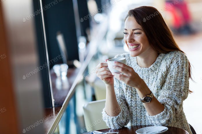 Young beautiful woman drinking coffee in restaurant